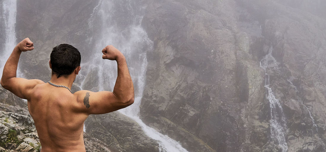 Rear view of shirtless muscular man flexing muscles while looking at waterfall