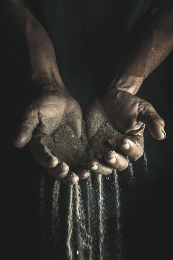 Cropped hands of man holding sand against black background