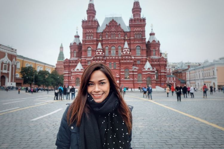 Portrait Of Smiling Woman Standing At Red Square In City