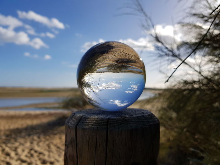 Close-up of crystal ball on wooden table against sky