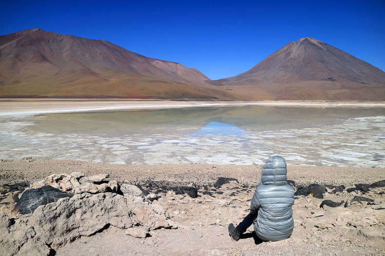 Woman sitting on the shore waiting for the green water effect of Laguna Verde or the Green Lake with Lincancabur Volcano in backdrop, Potosi, Bolivia Mountain Tranquil Scene Beauty In Nature Water Scenics - Nature Lake Tranquility Sky Nature Mountain Range Day Land Clear Sky Blue Rock Non-urban Scene Sunlight Environment Salt Flat Arid Climate Woman Travel Lagoon Green Laguna Verde International Women's Day 2019