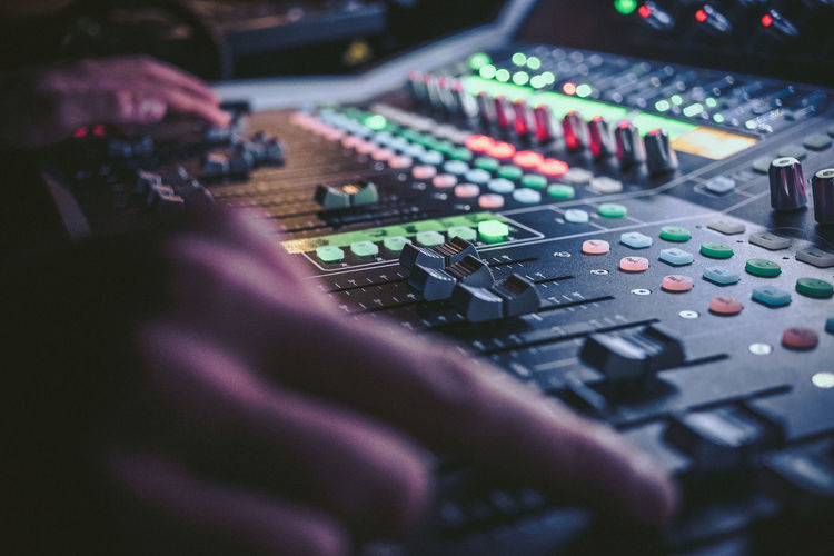 Cropped hands of dj operating sound recording equipment