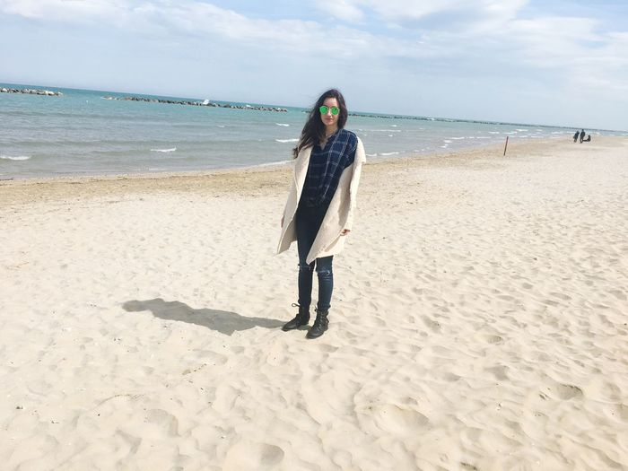 Portrait of young woman wearing sunglasses while standing at beach against sky during sunny day