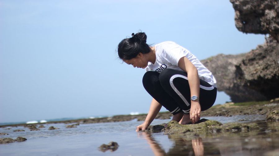 Woman crouching on rock at beach against sky