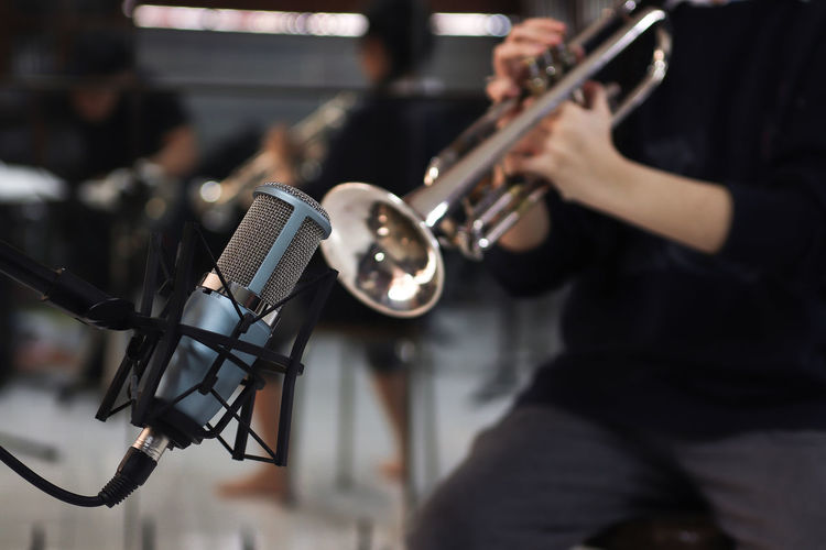 Microphone on Trumpet background Music Musical Instrument Arts Culture And Entertainment Musician Focus On Foreground Artist Performance Musical Equipment Playing Occupation Holding People Human Hand Human Body Part Indoors  Input Device Hand Microphone Skill  Incidental People Orchestra