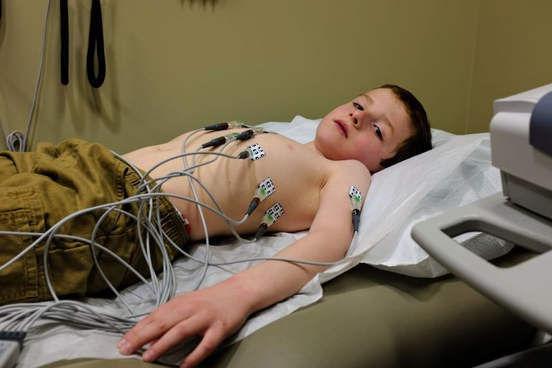 Shirtless Boy With Medical Equipment On Chest Lying At Bed In Hospital