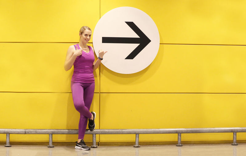 Full length of woman standing against yellow wall