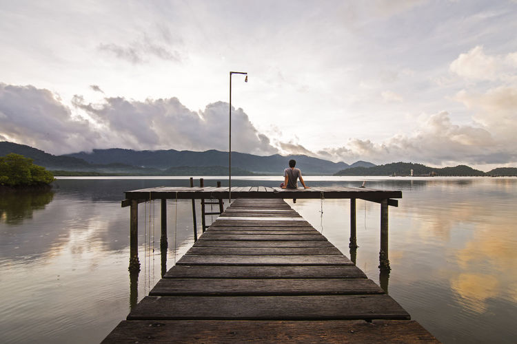 Rear view of man sitting on pier over lake