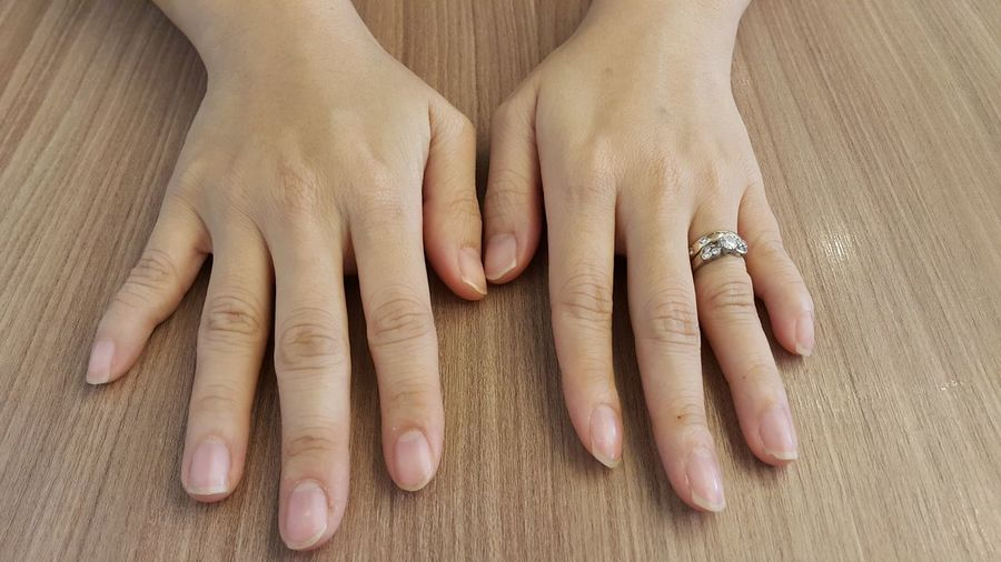 Cropped Image Of Hands With Ring On Wooden Table