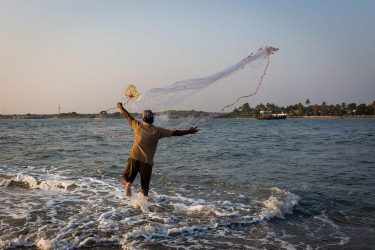 Full length of shirtless man fishing in sea against sky