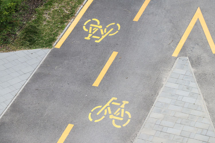 Bike path Architecture Arrow Symbol City Communication Day Direction Disabled Access Disabled Sign Guidance High Angle View Marking No People Orthographic Symbol Outdoors Road Road Marking Road Sign Sign Symbol Text Transportation Yellow
