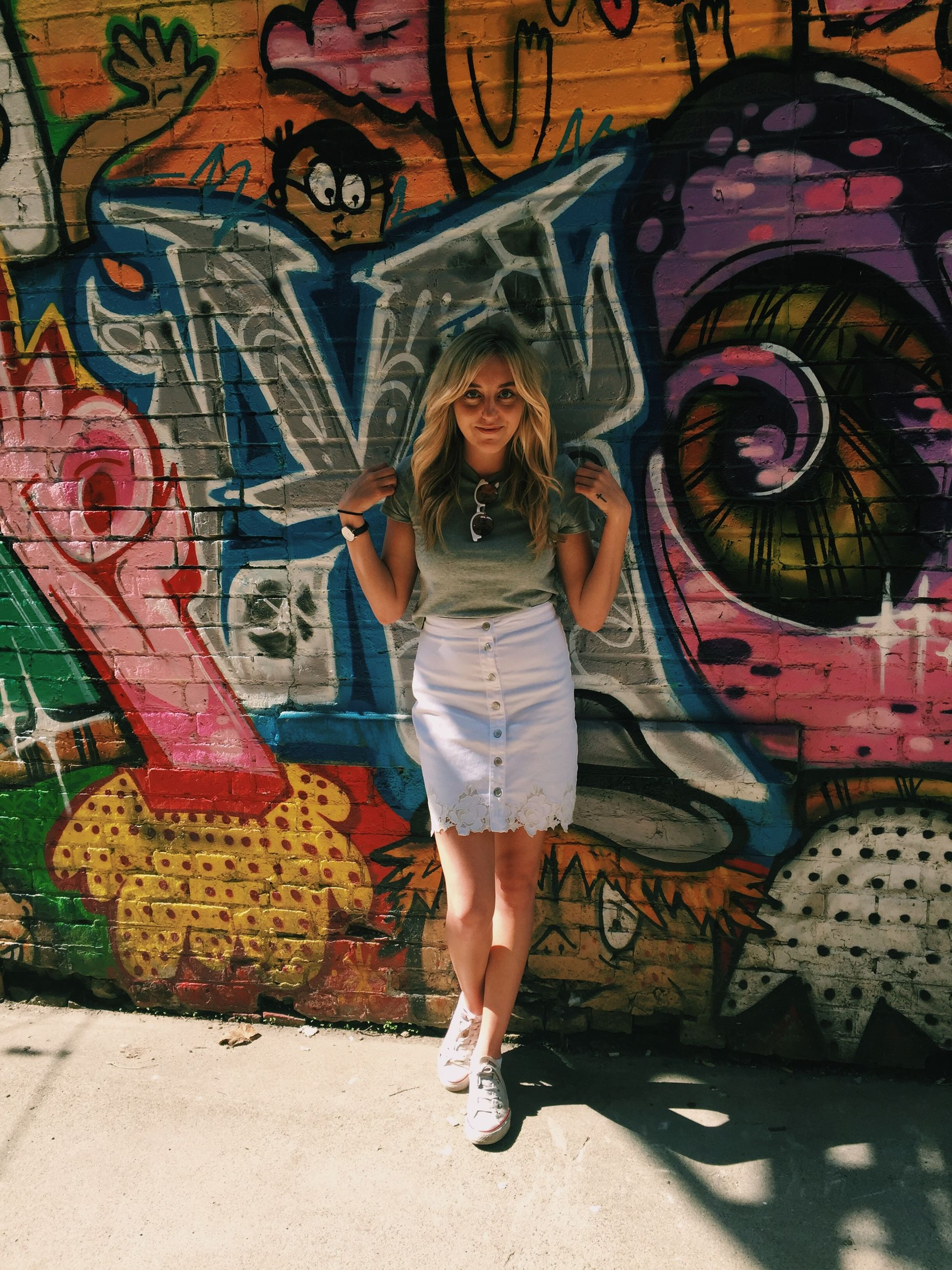 one person, front view, graffiti, full length, standing, creativity, art and craft, smiling, women, real people, happiness, looking at camera, casual clothing, lifestyles, portrait, child, wall - building feature, young adult, mural, hairstyle