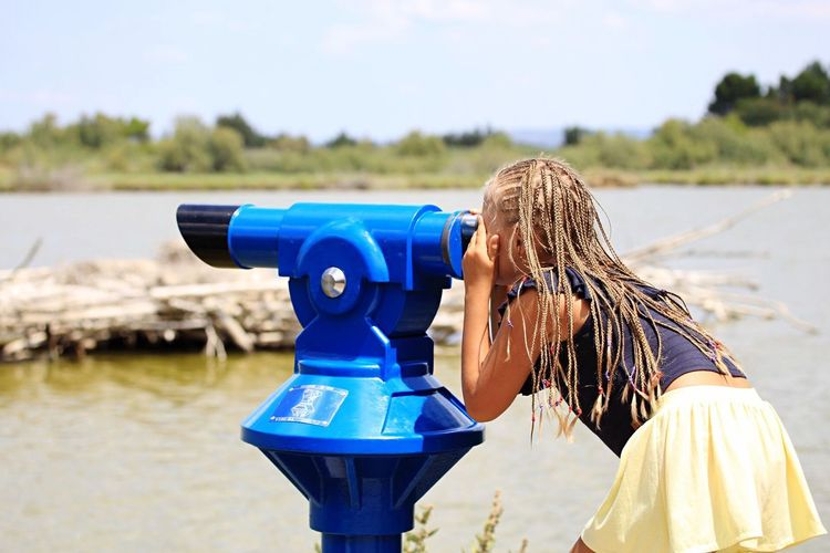 EyeEm Selects Water Outdoors Day One Person Blond Hair Focus On Foreground Side View Coin-operated Binoculars Standing Blue Nature Sky Technology Travel Destinations African Braid