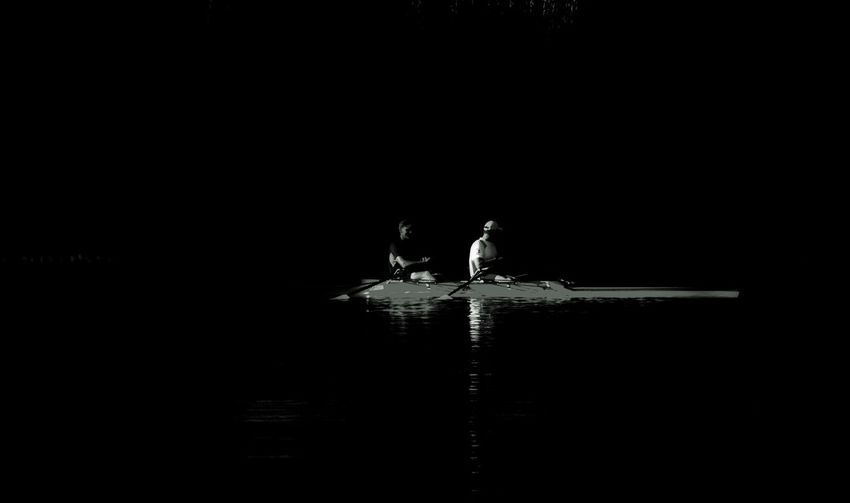 Silhouette people standing by lake at night