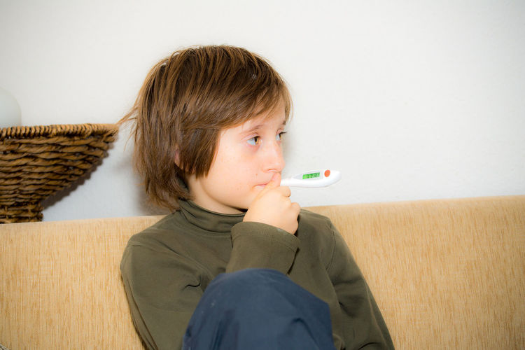 Boy with fever measures his temperature Winter Child Cold Fever Flu Healthy Eating Indoors  One Person Sickness Sitting Temperature Thermometer Virus