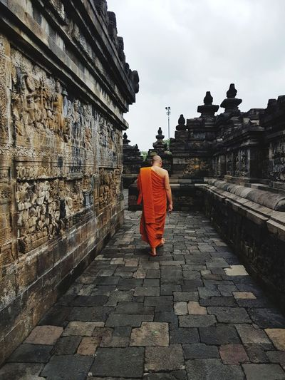 Rear View Of Monk Walking On Footpath By Temple Against Sky