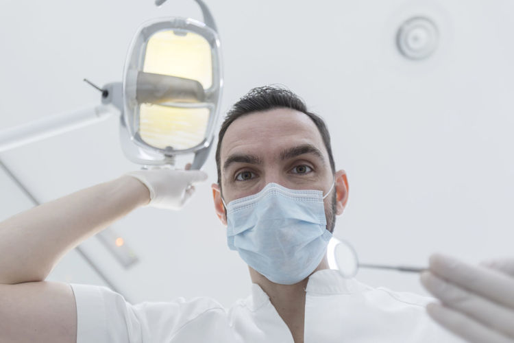 Low Angle Portrait Of Doctor Wearing Surgical Mask At Hospital