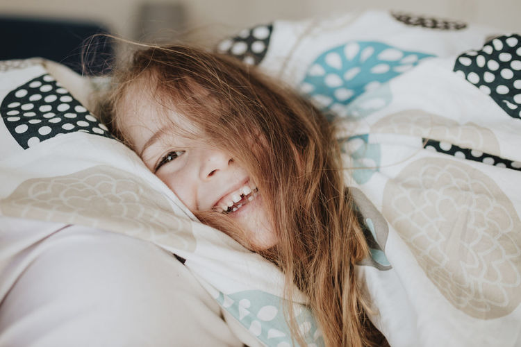 Portrait of happy girl lying on bed