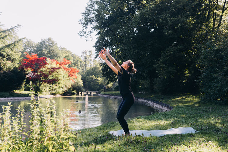 Full length of woman standing by lake against trees doing yoga