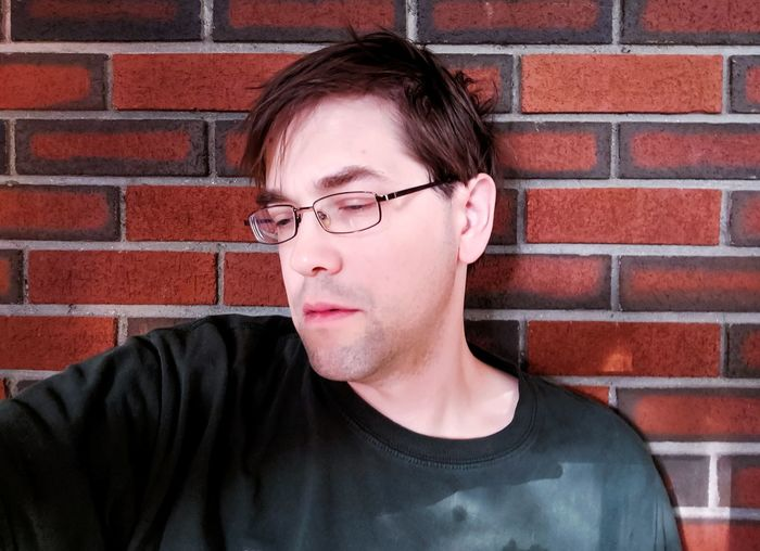 Portrait of young man wearing eyeglasses against brick wall