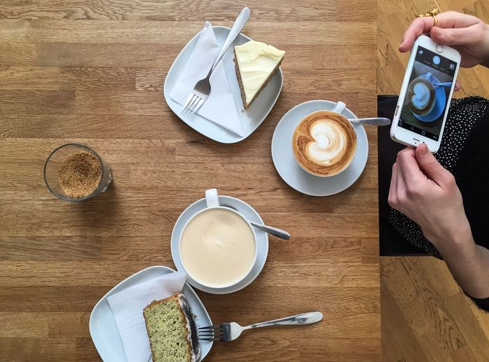 Midsection of woman photographing coffee while sitting at table