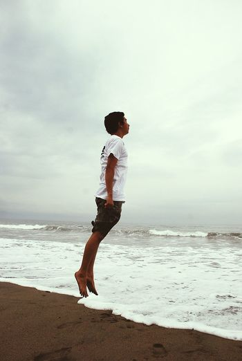 Side View Of Man Jumping At Beach Against Sky