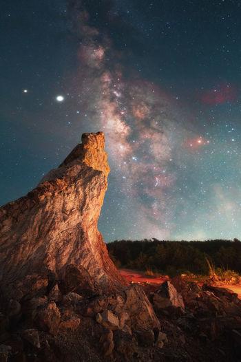 Rock formation on landscape against sky at night