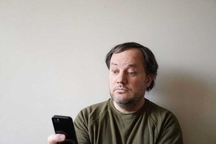 Man using phone against wall