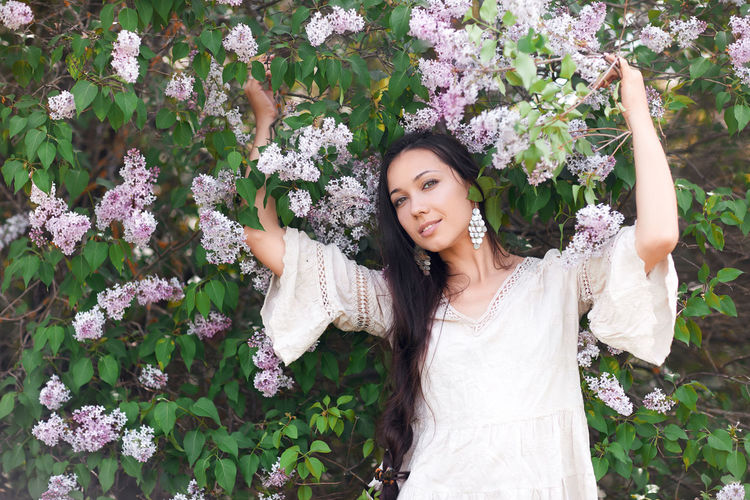 Portrait of smiling woman standing by white flowering plants