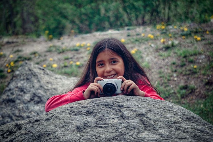 Portrait of smiling girl holding camera over rock