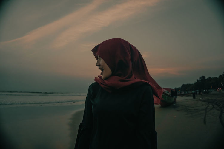 Woman wearing hijab enjoying at beach against sky during sunset