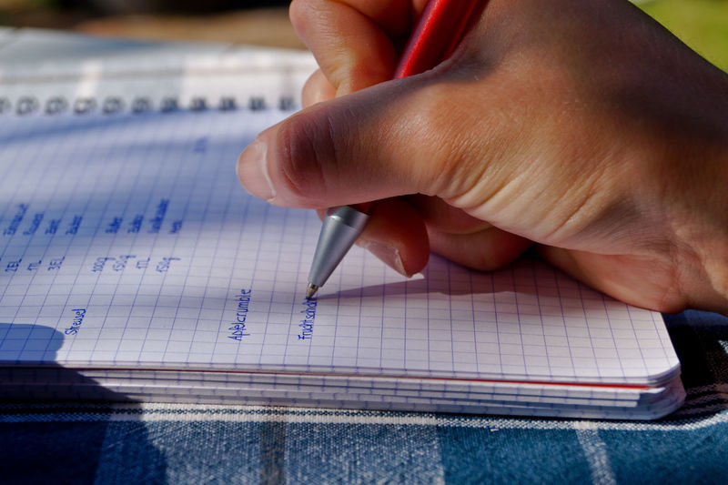 Cropped image of woman writing on book at table