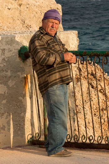 Side View Of Mature Man Standing By Rusty Railing On Sunny Day