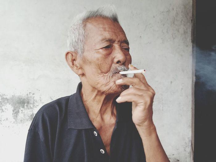 Senior man smoking cigarette against wall