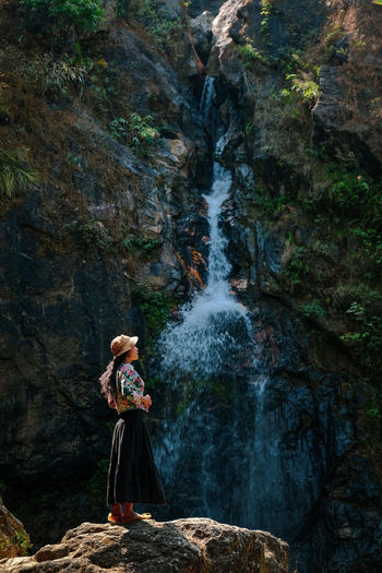 Woman standing on rock against waterfall in forest