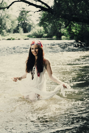 Young woman walking in a river One Person Real People Young Adult Front View Women Lifestyles Leisure Activity Young Women Nature Beauty Portrait Long Hair Beautiful Woman Water Looking At Camera Hair Standing White Color Hairstyle Fashion Outdoors Boho Hippie Freedom Girl