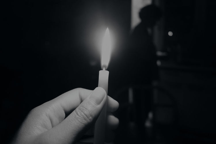 Cropped hand holding illuminated candle