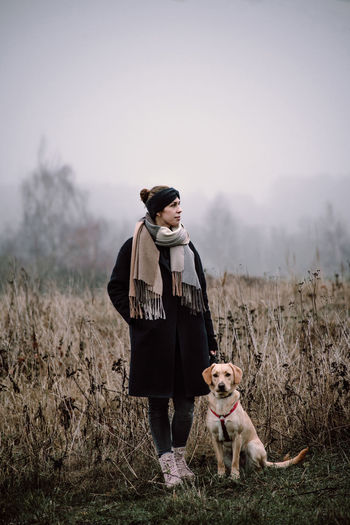 Dog One Animal Animal One Person Front View Adult Clothing Field Grass Warm Clothing Pet Owner Dog Love Fashion Style Young Women Young Adult Monochrome Nature Naturelovers Canine Casual Clothing Outdoors Fog Portrait Candid Portraits