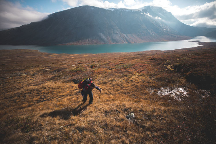 Man climbing on mountain against lake