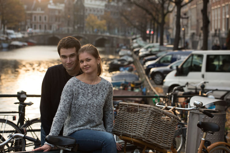 Portrait of smiling friends by bicycle in city
