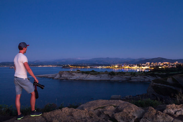 Enjoying nightfall Blue Hour Camera Lost In The Landscape Nature Nature Photography Beauty In Nature Casual Clothing City Lights City Photography Holding Leisure Activity Lifestyles Men Nature Nightfall Observing One Person Outdoors People Rear View Scenics Standing Water Young Adult