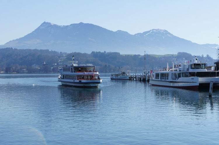 Boats on Lake Lucerne Alps Switzerland Beauty In Nature Boat Clear Sky Day Ferry Lake Lucerne Mode Of Transport Moored Mountain Mountain Range Nature Nautical Vessel No People Outdoors River Sailing Scenics Sky Tranquility Transportation Travel Destinations Water Waterfront