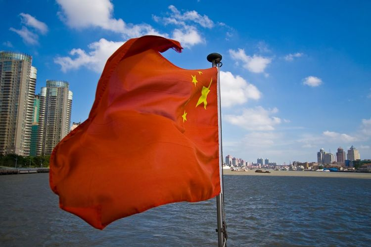 Chinese flag by sea in city against sky
