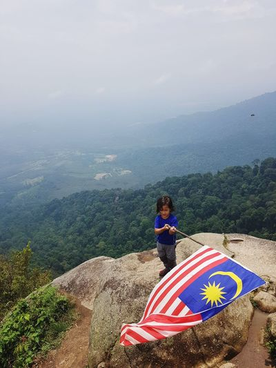 a kid with malaysia flag Happy Hiking Adventure Nature Malaysia Mountain View Flag Girl Celebration Hikingadventures Peak Tree Child Forest Beauty Hill Summer Sky Landscape Hiker Mountain Range Rocky Mountains Mountain Mountain Peak