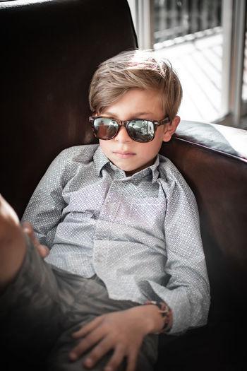 Portrait of boy wearing sunglasses sitting outdoors