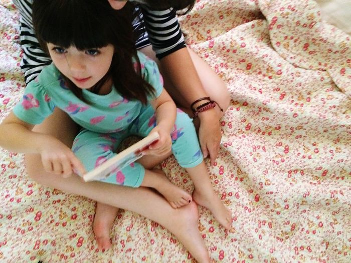High angle view of cute girl holding book while sitting on mother laps at bed