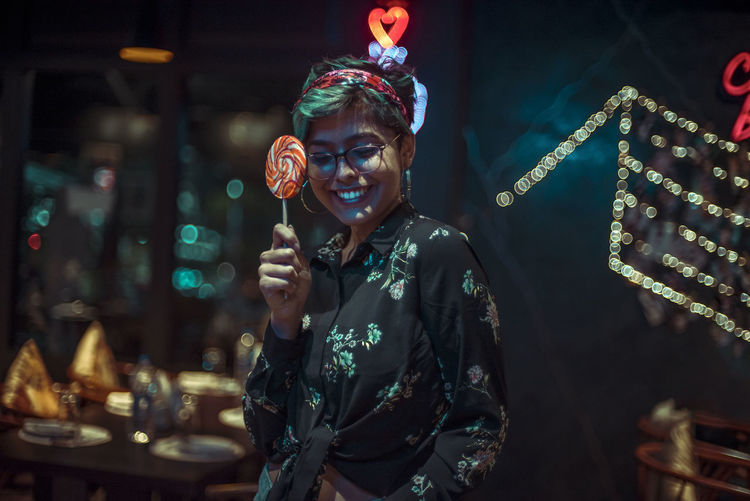 Smiling woman holding lollipop while standing in illuminated city at night