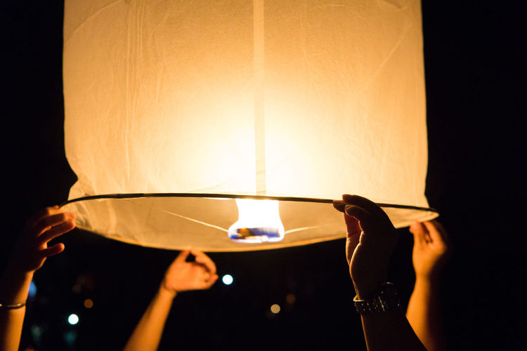 Friends holding paper lantern at night