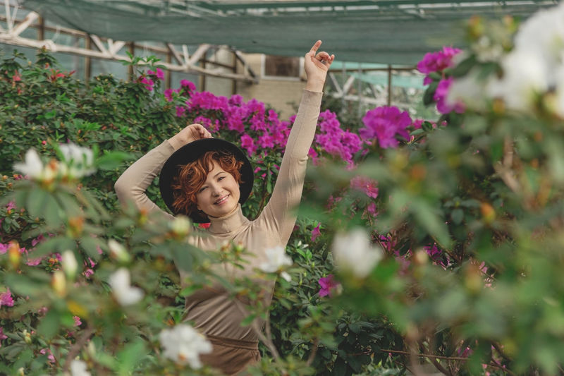 A beautiful plus size girl in a hat smiles among the green plants of greenhouse
