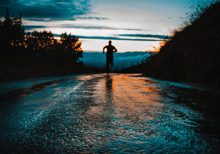 Surface level shot of silhouette man running on wet road against sky during sunset
